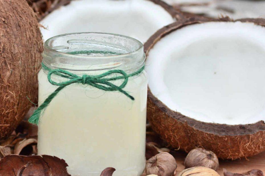 Ein Glas mit Kokosöl umgeben von Kokosnüssen.