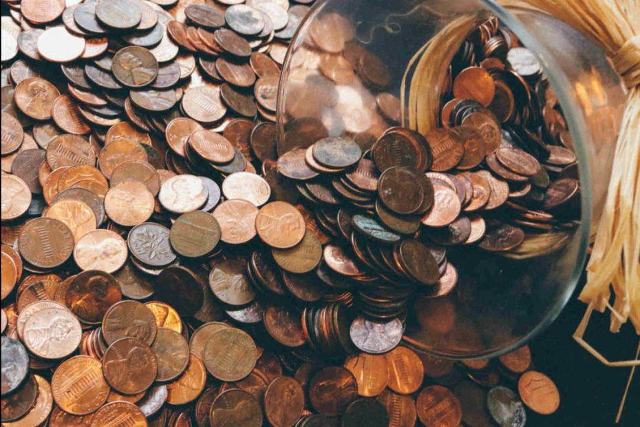 Ein umgefallenes Glas mit Kupfergeldmünzen.